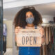 Woman holding Open sign in a small business boutique shop after Covid-19 pandemic