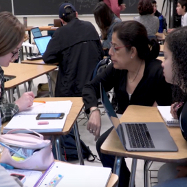 professor helping students as their desk.