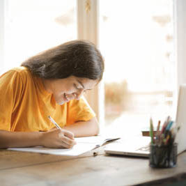 A smiling girl writing in a booklet on a desk with an opened laptop.